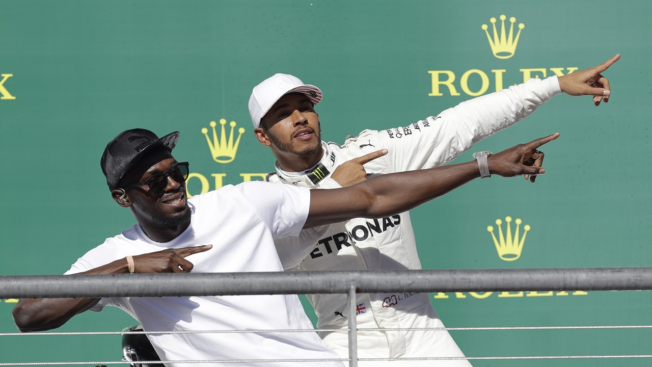 Sprinter Usain Bolt, left, and Mercedes driver Lewis Hamilton, of Britain, pose after Hamilton won the Formula One U.S. Grand Prix auto race at the Circuit of the Americas, Sunday, Oct. 22, 2017, in Austin, Texas. (AP Photo/Darron Cummings)