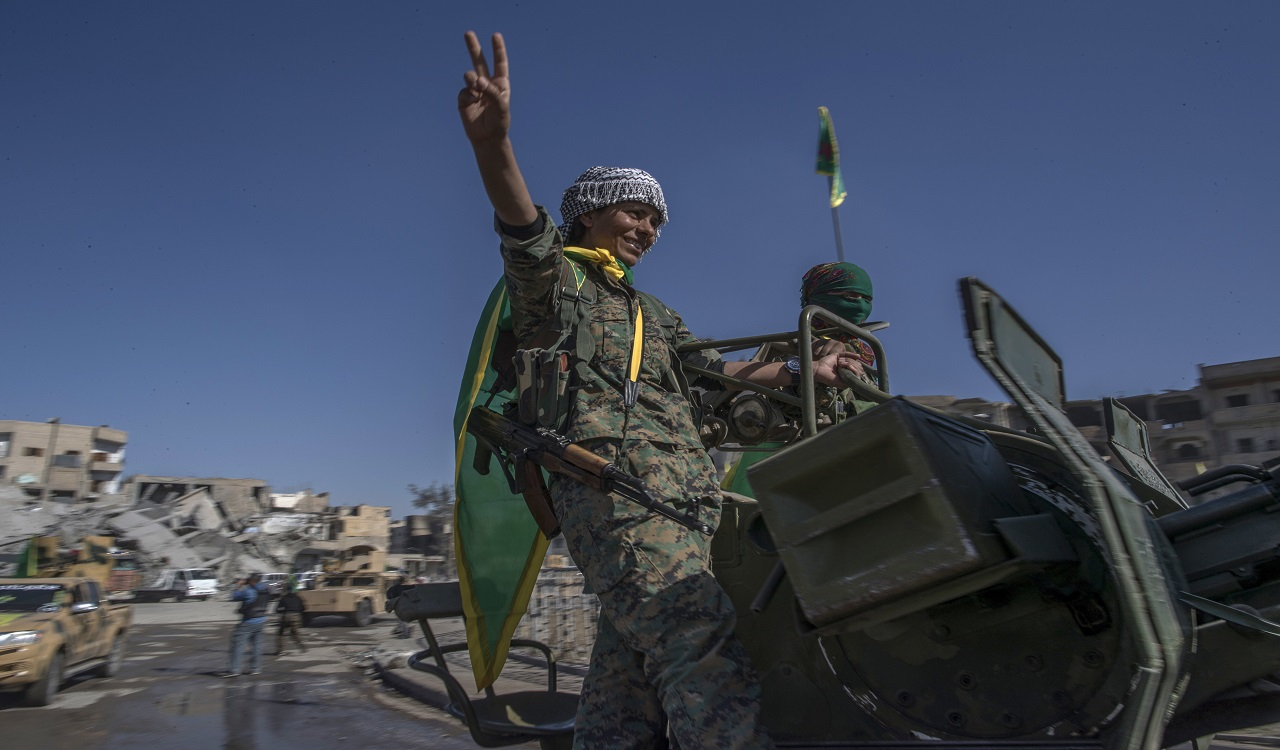 In this Thursday, Oct. 19, 2017 photo, fighters from the Women's Protection Units, or YPJ, hold a celebration in Paradise Square in Raqqa, Syria. The Kurdish female militia that took part in freeing the northern Syrian city of Raqqa from the Islamic State group said on Thursday it will continue the fight to liberate women from the extremists' brutal rule.