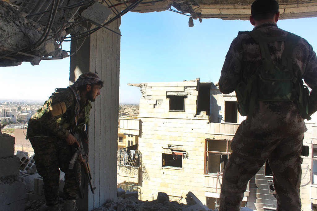 In this picture taken on Monday Oct. 16, 2017 and provided by The Syrian Democratic Forces (SDF), a U.S.-backed Syrian Kurdish forces outlet that is consistent with independent AP reporting, shows Syrian Democratic Forces (SDF) fighters, take their position on a destroyed building during their battle against the Islamic State militants, in Raqqa, Syria. (Syrian Democratic Forces, via AP)