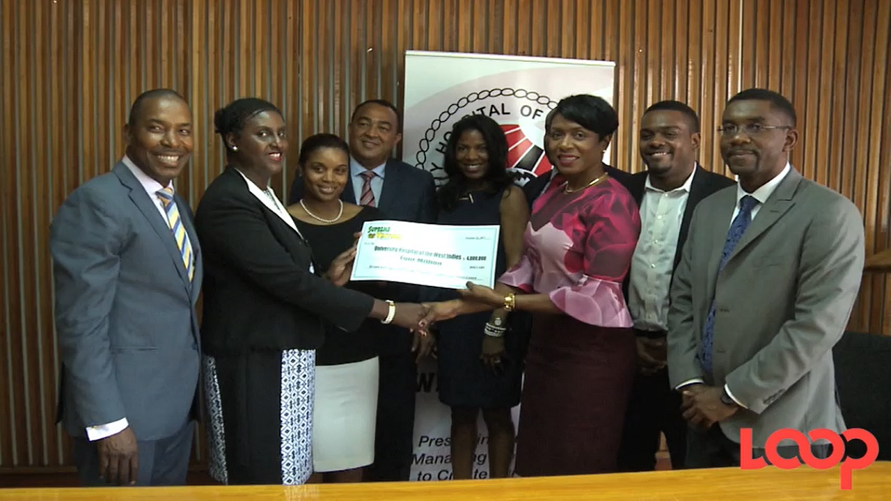 Supreme Ventures Limited president and CEO, Ann Dawn Young Sang, flanked by late CEO Brian George's widow and sons, hands over the cheque to the University Hospital of the West Indies.