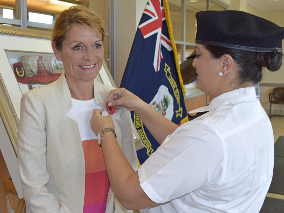 Governor of Cayman, Her Excellency Helen Kilpatrick being pinned with a poppy by former US Marine and member of CIVA Ms Shane McLaughlin.