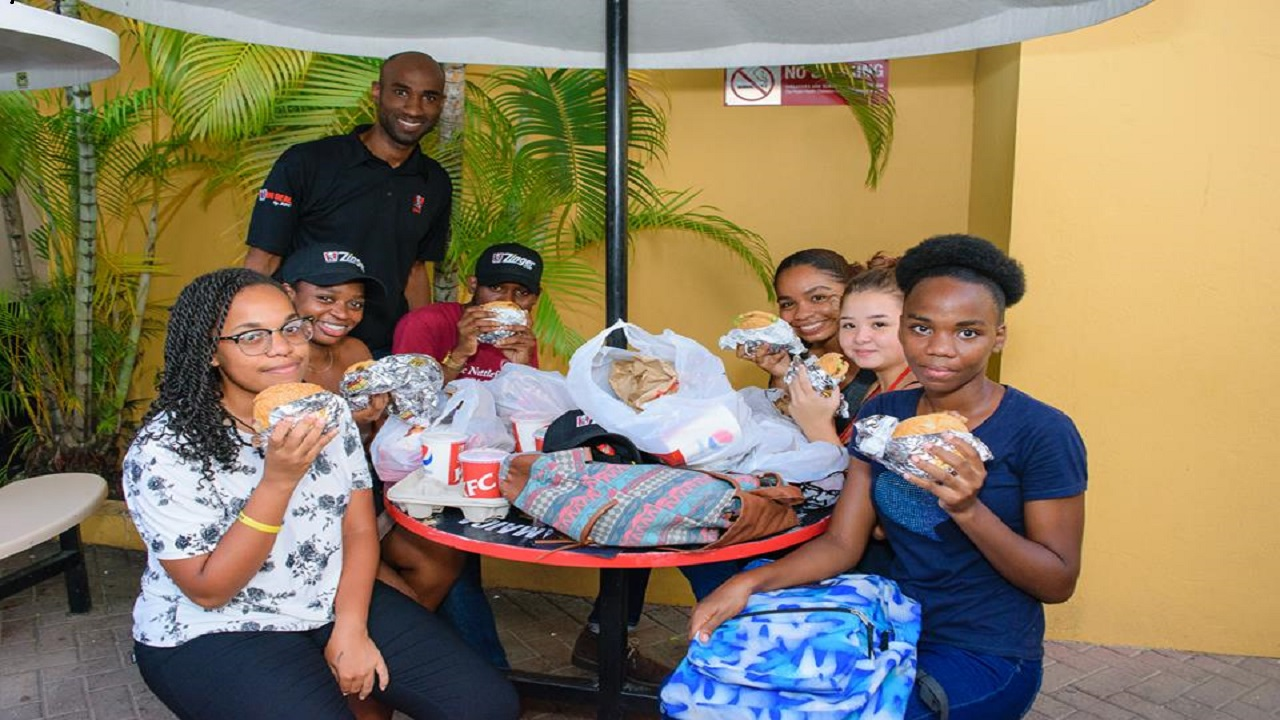 Andrei Roper, KFC Jamaica Brand Manager (standing) shares a moment with a few UWI, Mona students.