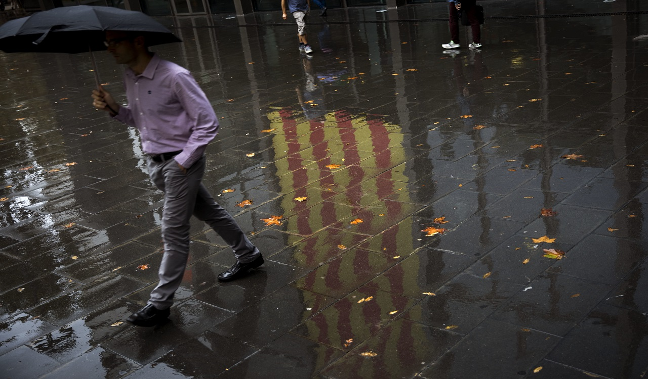 People walk past a Catalan flag reflected on the wet ground in Barcelona, Spain, Thursday, Oct. 19, 2017.