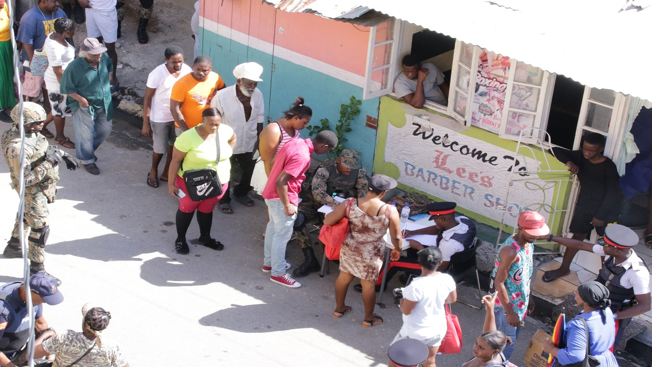 Denham Town residents being processed by members of the security forces after the community was declared a ZOSO on Tuesday.