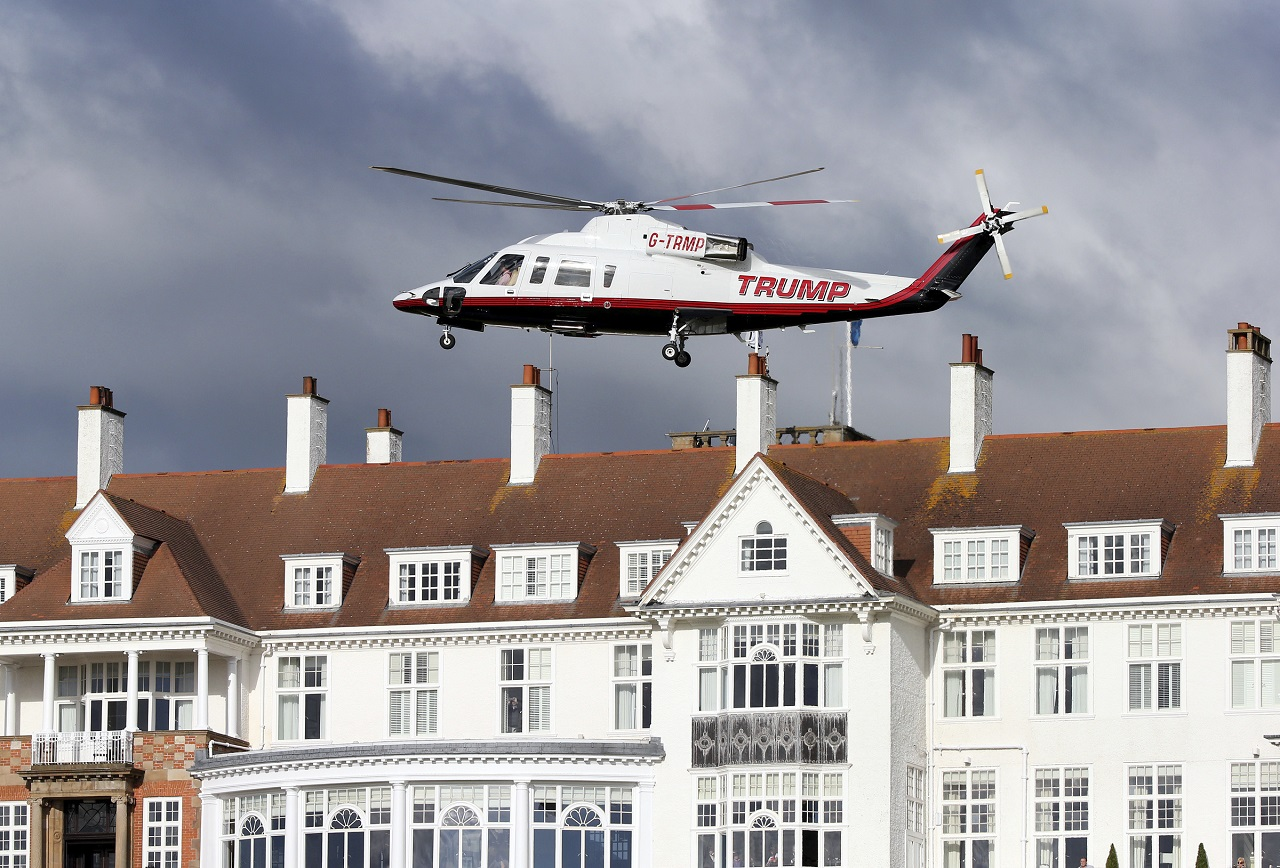 In this July 29, 2015 file photo, a helicopter owned by Donald Trump departs from the Turnberry golf course in Turnberry, Scotland, A financial report filed with the British government shows Donald Trump is losing millions for a third year in a row on a couple of his biggest investments: his Scottish golf resorts.
