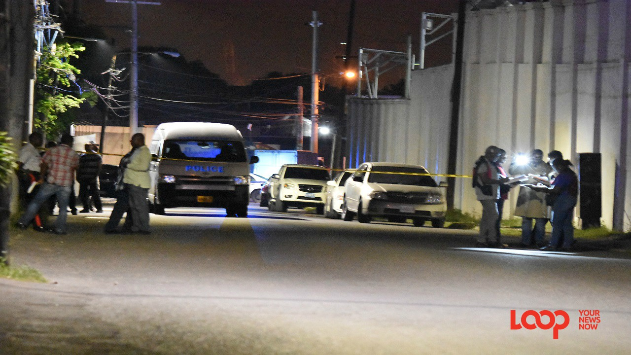 Police officers process the scene where businessman Dennis Ramdial was shot dead on Monday. (PHOTO: Marlon Reid)