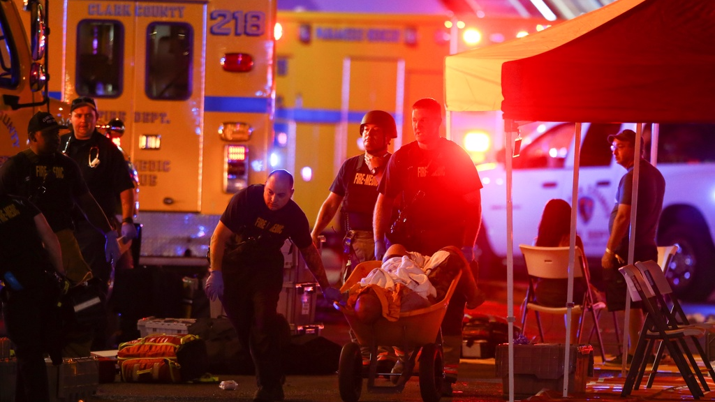 wounded person is walked in on a wheelbarrow as Las Vegas police respond during an active shooter situation on the Las Vegas Stirp in Las Vegas Sunday, Oct. 1, 2017. Multiple victims were being transported to hospitals after a shooting late Sunday at a music festival on the Las Vegas Strip. (Chase Stevens/Las Vegas Review-Journal via AP)