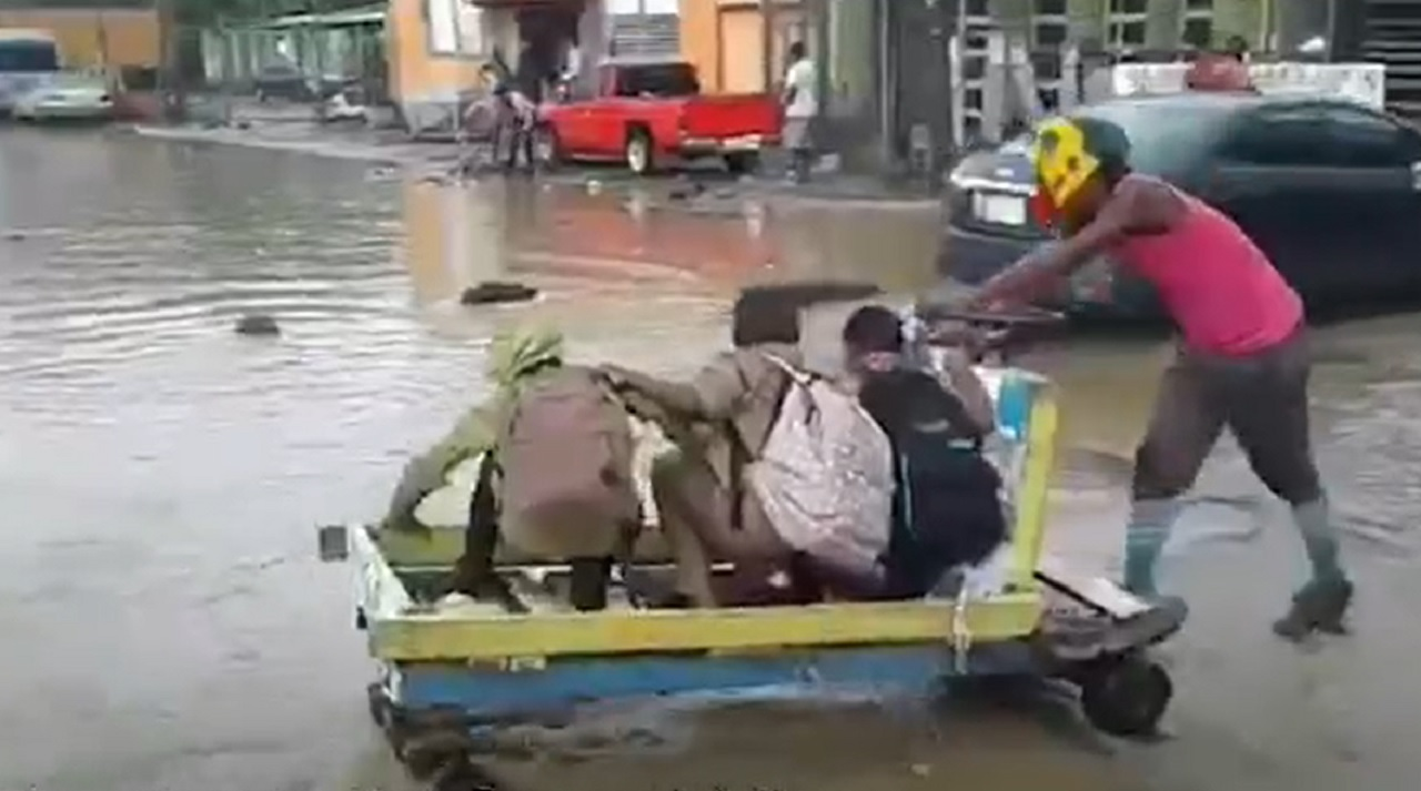 School children being transported by handcart in flooded Montego Bay on Friday.