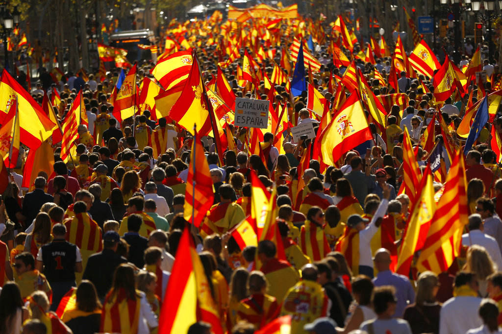 Demonstrators holding mostly Spanish flags march to protest the Catalan government's push for secession from the rest of Spain at a coffeeshop in downtown Barcelona, Spain, Sunday Oct. 8, 2017. Sunday's rally comes a week after separatist leaders of the Catalan government held a referendum on secession that Spain's top court had suspended and the Spanish government said was illegal.(AP Photo/Francisco Seco)