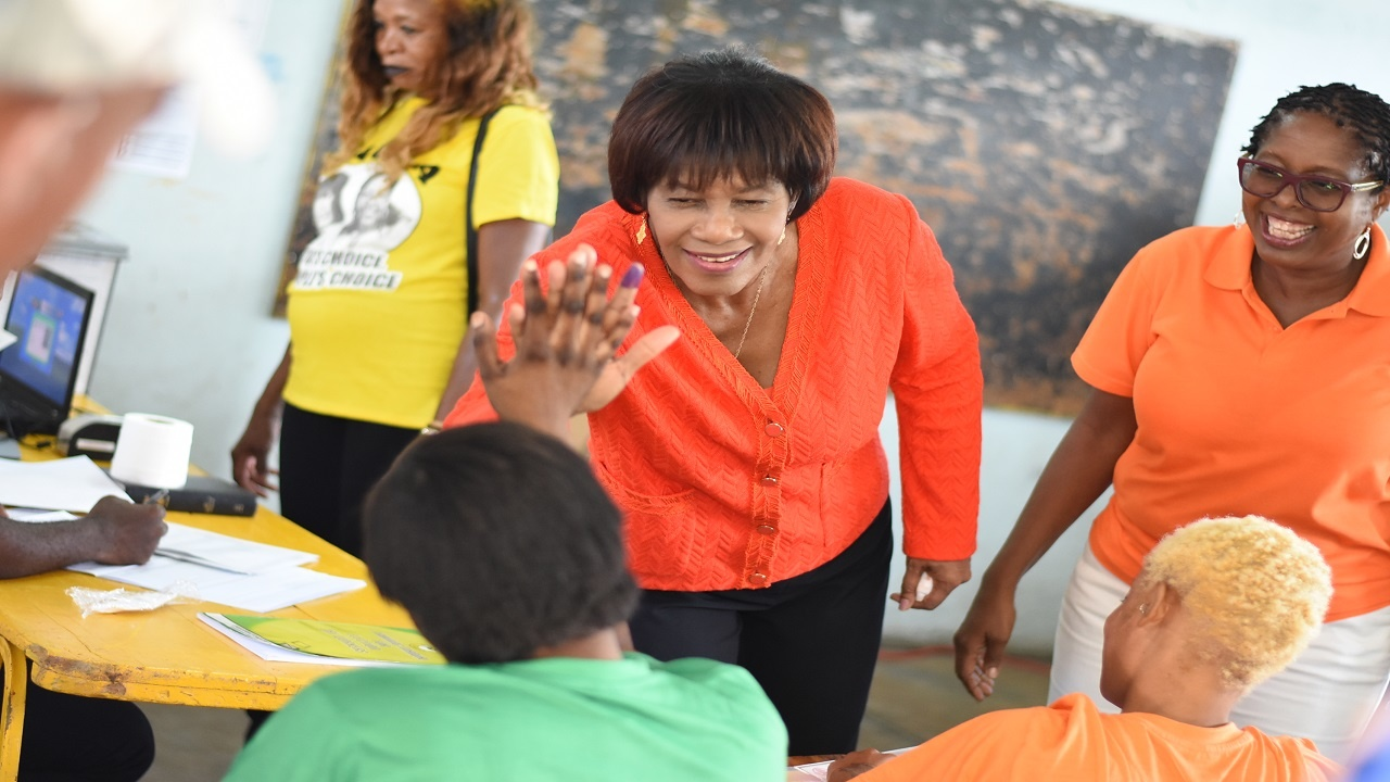 Former MP for South West St Andrew Portia Simpson Miller 'high fives' a woman clad in green while PNP candidate for the constituency, Angela Brown Burke, looks on during voting in the by-election on Monday. (PHOTO: Marlon Reid)