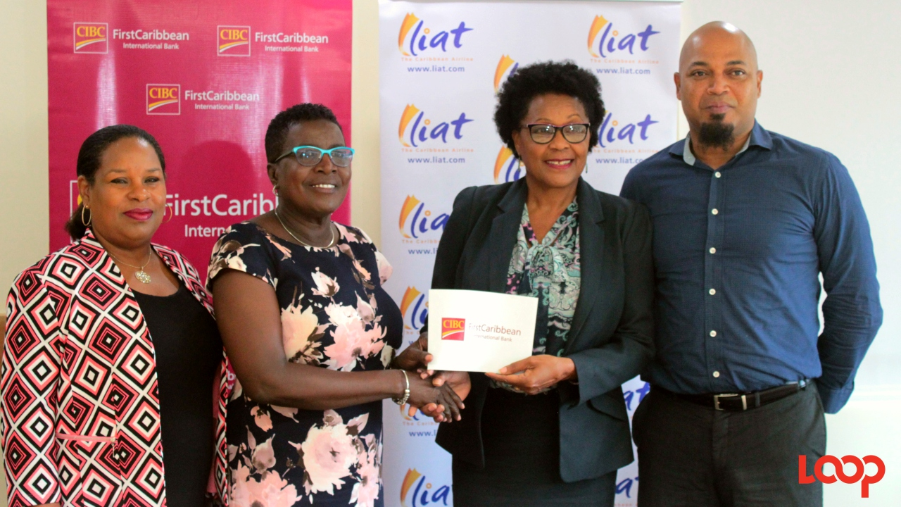 LIAT CEO Julie Reifer-Jones (second right) accepts a donation from Trustee of FirstCaribbean International Comtrust Foundation Limited, Lynda Goodridge, as Debra King, CIBC FirstCaribbean Director of Corporate and Communications (left) and Egbert Riley, LIAT Head of Sales and Marketing, look on at a press briefing at the Barbados headquarters this afternoon.