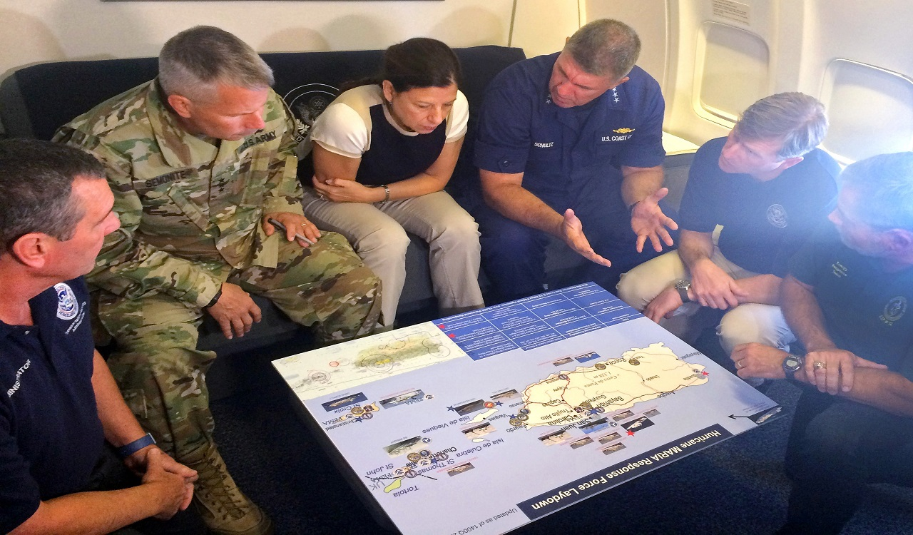Acting Homeland Secretary Elaine Duke, center, is briefed on the Hurricane Maria response during a flight to Puerto Rico on Friday, Sept. 29, 2017.