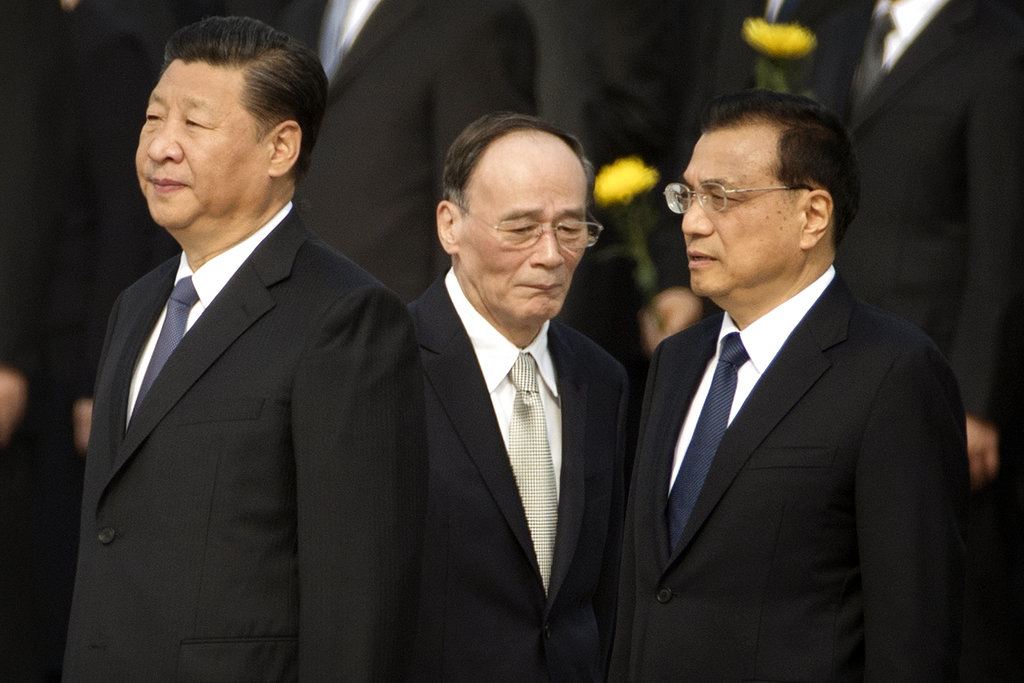 In this Sept. 30, 2017 file photo, Chinese President Xi Jinping, left, Politburo Standing Committee member Wang Qishan, center, and Chinese Premier Li Keqiang attend a ceremony marking Martyrs' Day at Tiananmen Square in Beijing. Having bested his rivals, Chinese President Xi is primed to consolidate his already considerable power as the country's ruling Communist Party begins its twice-a-decade national congress on Wednesday, Oct. 18. (AP Photo/Mark Schiefelbein, File)