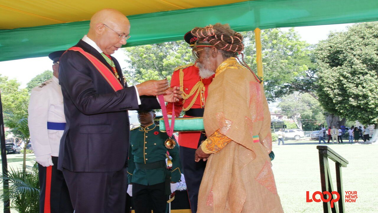 Neville O'Reilly Livingstone, popularly known as 'Bunny Wailer', collects his award from Governor General Sir Patrick Allen at King's House on Monday. (PHOTOS: Llewellyn Wynter)