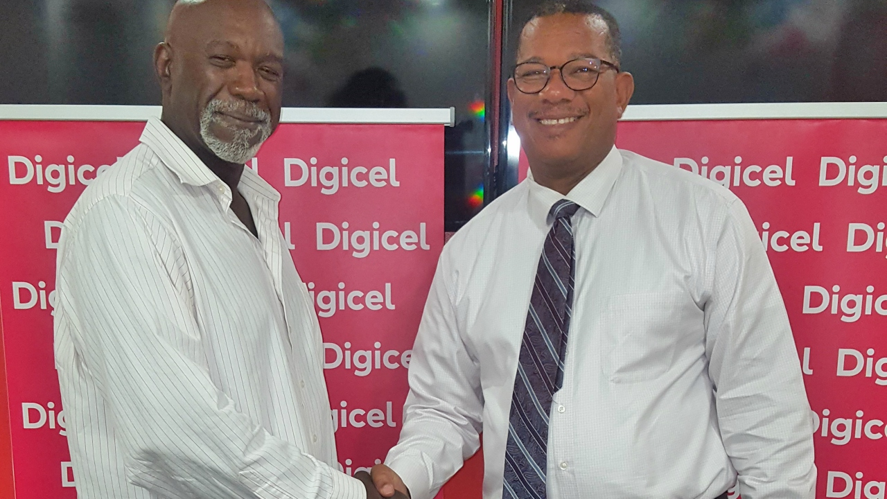 Digicel's CEO Alex Tasker (right) speaking to Phillipe Taitt of New Covenant, during the handover of uniforms to some of the students.