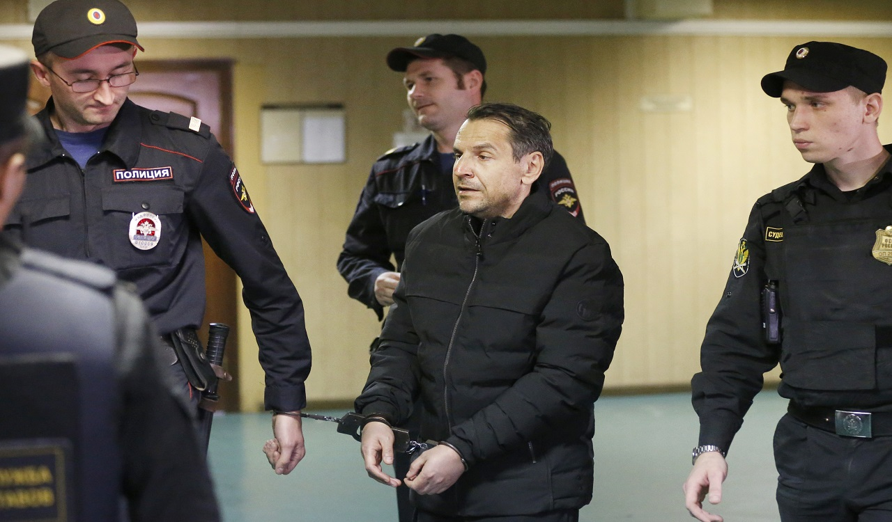 Boris Grits, 48, who holds Russian and Israeli citizenship, centre, is escorted by police officers as he arrives at a courthouse in Moscow, Russia, Tuesday, Oct. 24, 2017. The Investigative Committee has identified Boris Grits as the assailant of Tatyana Felgenhauer, a top host and deputy editor-in-chief at Russia's only independent news radio station who was stabbed at the station's studios on Monday, the latest of a string of attacks on journalists and opposition activists in Moscow.