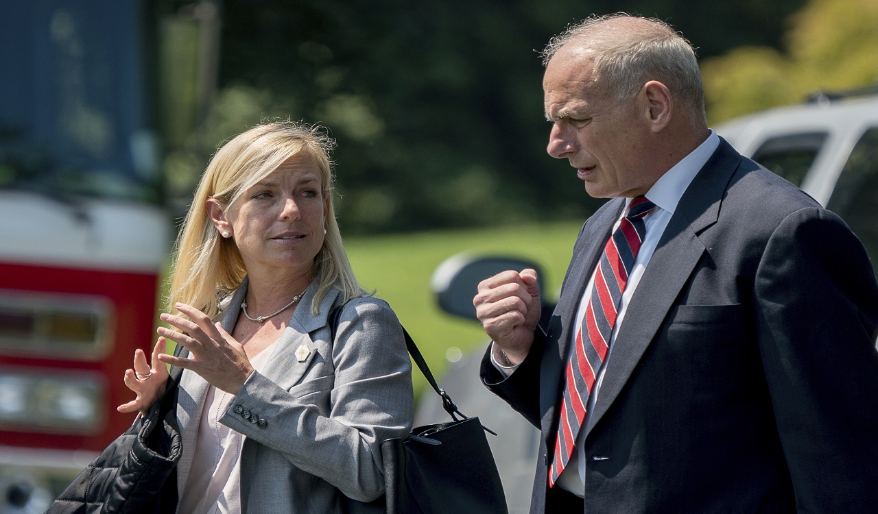 In this Aug. 22, 2017 photo, White House Chief of Staff John Kelly and Deputy Chief of Staff Kirstjen Nielsen speak together as they walk across the South Lawn of the White House in Washington.
