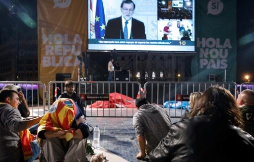 AFP / CESAR MANSO Des Catalans écoutent un discours télévisé du Premier ministre espagnol Mariano Rajoy après le référendum sur l'indépendance de la Catalogne, le 1er octobre 2017 à Barcelone