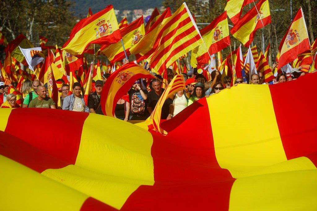 Nationalist activists protest with Spanish and Catalan flags during a mass rally against Catalonia's declaration of independence, in Barcelona, Spain, Sunday, Oct. 29, 2017. Thousands of opponents of independence for Catalonia held the rally on one of the city's main avenues after one of the country's most tumultuous days in decades.(AP Photo/Santi Palacios)