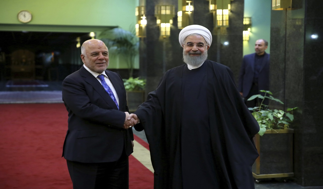 In this photo released by official website of the office of the Iranian Presidency, President Hassan Rouhani, right, welcomes Iraqi Prime Minister Haider al-Abadi for their meeting, in Tehran, Iran, Thursday, Oct. 26, 2017. Haider al-Abadi is in Iran after recent stops in Turkey and Jordan, and meetings with U.S. officials and allies eager to pull Baghdad into their political orbit.
