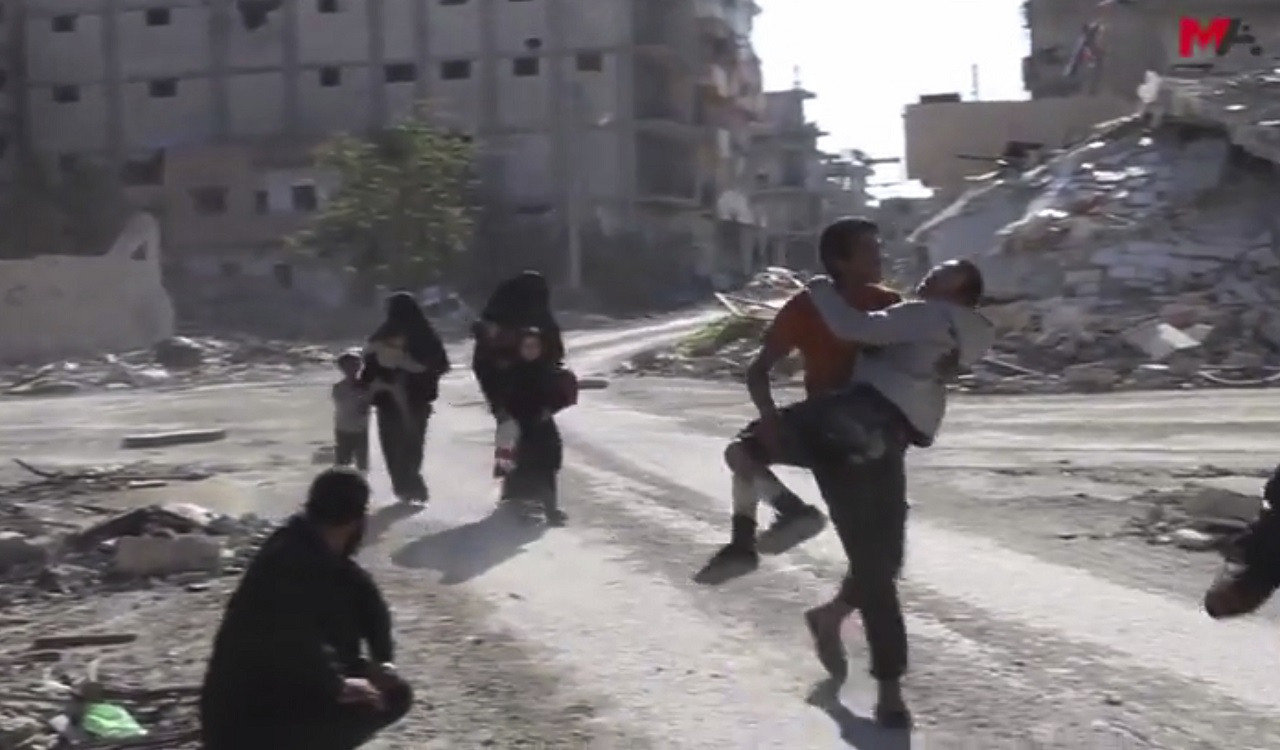This frame grab from a video provided on Friday, Oct. 13, 2017 by Turkey-based Kurdish Mezopotamya agency media outlet that is consistent with independent AP reporting, shows Syrian civilians run on a damaged street as they fleeing from the areas that still controlled by the Islamic State militants, in Raqqa, Syria.