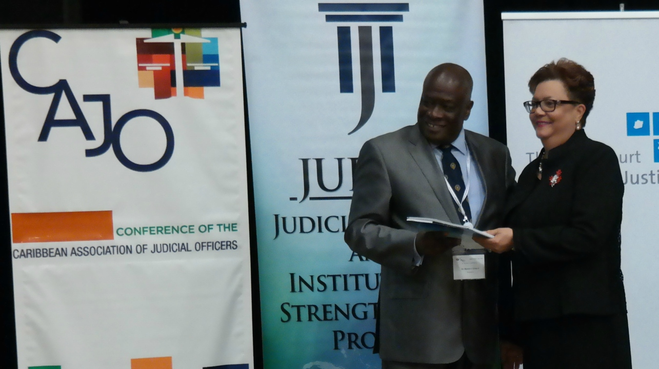 The Honourable Sir Marston Gibson, Chief Justice of Barbados receives a copy of the Model Guidelines for Sexual Offence Cases in the Caribbean Region from the Honourable Mme. Justice Maureen Rajnauth-Lee, Judge of the Caribbean Court of Justice at the launch of the Guidelines at the CAJO Conference in Curacao.