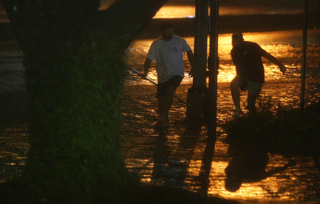 David Amerson, left, and T.J. Krueger, right, wade through a flooded street during Hurricane Nate, Sunday, Oct. 8, 2017, in Mobile, Ala. Hurricane Nate came ashore along Mississippi's coast outside Biloxi early Sunday, the first hurricane to make landfall in the state since Hurricane Katrina in 2005. (AP Photo/Brynn Anderson)