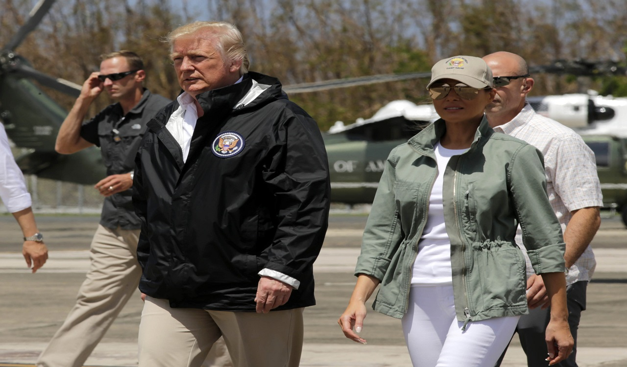 In this Oct. 3, 2017, photo, President Donald Trump and first lady Melania Trump walk after arrival at the Luis Muñiz Air National Guard Base in San Juan, Puerto Rico.