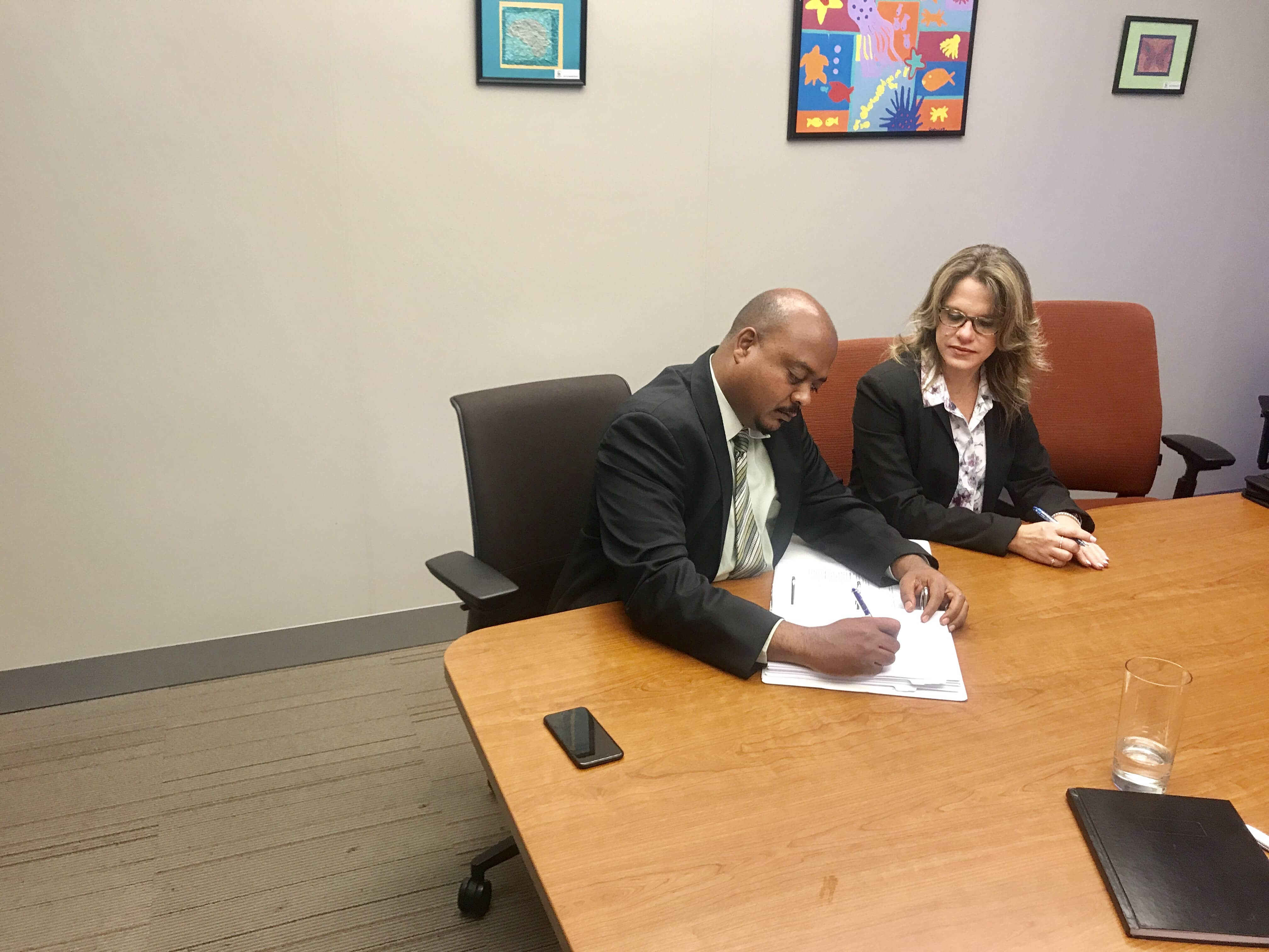 Chief Officer for Education, Christen Suckoo signs the contract with KPMG Partner, Sheenah Hislop.