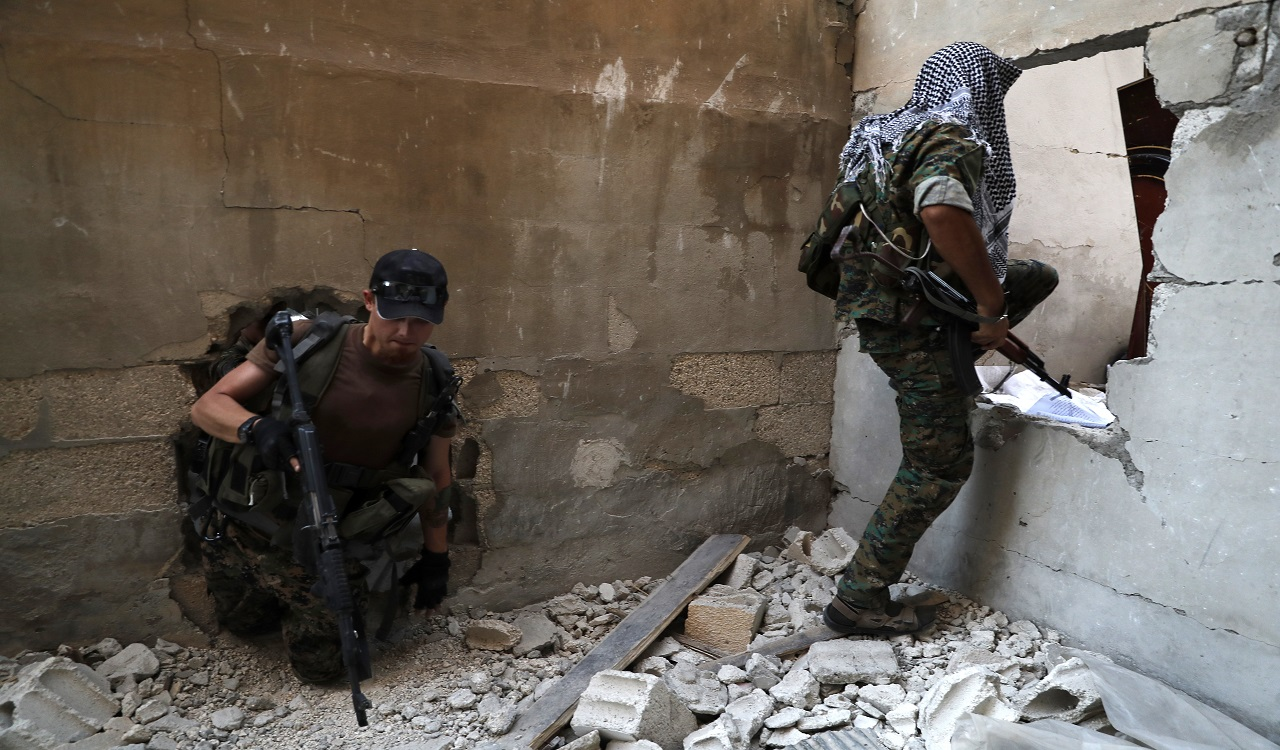 In this July 27, 2017 file photo, U.S.-backed Syrian Democratic Forces fighters, pass through holes as they cross from building to building to hide from snipers, on the front line with Islamic State group militants, in Raqqa, Syria.
