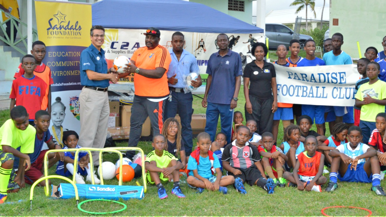 Sandals Barbados GM Fernand Zievinger (left) presents coach of the Paradise Youth Football Club, Rudy Pinder, with some of the sports equipment from Sandals Foundation.