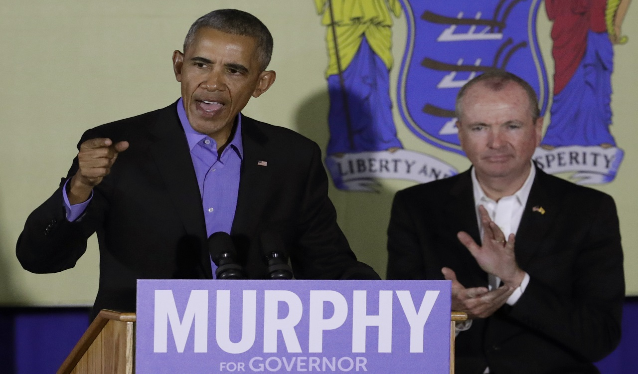 Former President Barack Obama, left, speaks during a canvassing event for New Jersey Democratic gubernatorial nominee Phil Murphy, right, Thursday, Oct. 19, 2017, in Newark, N.J.