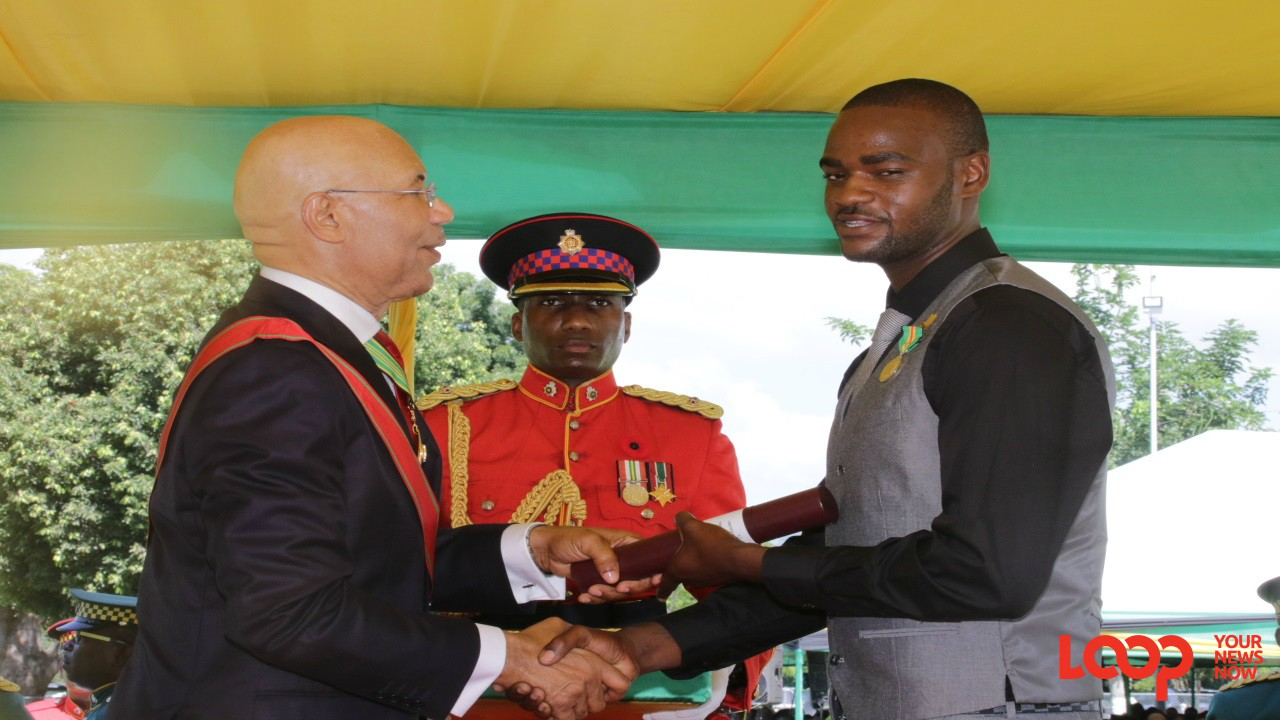 Tremayne Brown collects his national award from Governor General Sir Patrick Allen at Kings House on Monday. (PHOTOS: Llewellyn Wynter)