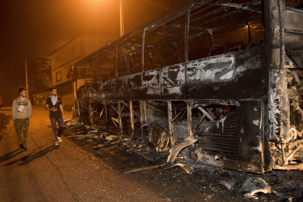Residents walk past a burnt bus as a wild fire moves forward in Chandebrito, Pontevedra, in the northwestern Spanish region of Galicia, Spain on Monday, Oct. 16, 2017. Authorities in Portugal and Spain say that nine people died over the weekend in hundreds of wildfires fanned by strong winds caused by a hurricane. Three people, two of whom were trapped in a car, were killed as a result of more than 130 blazes reported in different areas, officials said. (AP Photo/Alba Sotelo)