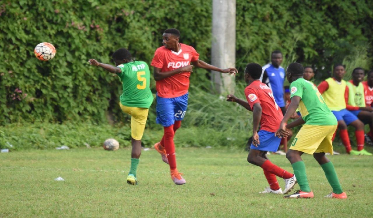 substitute Damion Herrera (left) of St Jago High takes a shot during the Group F top-of-the-table ISSA/FLOW Manning Cup match against Holy Trinity at the Bell Chung Oval on Tuesday. The match ended in a 1-1 draw.