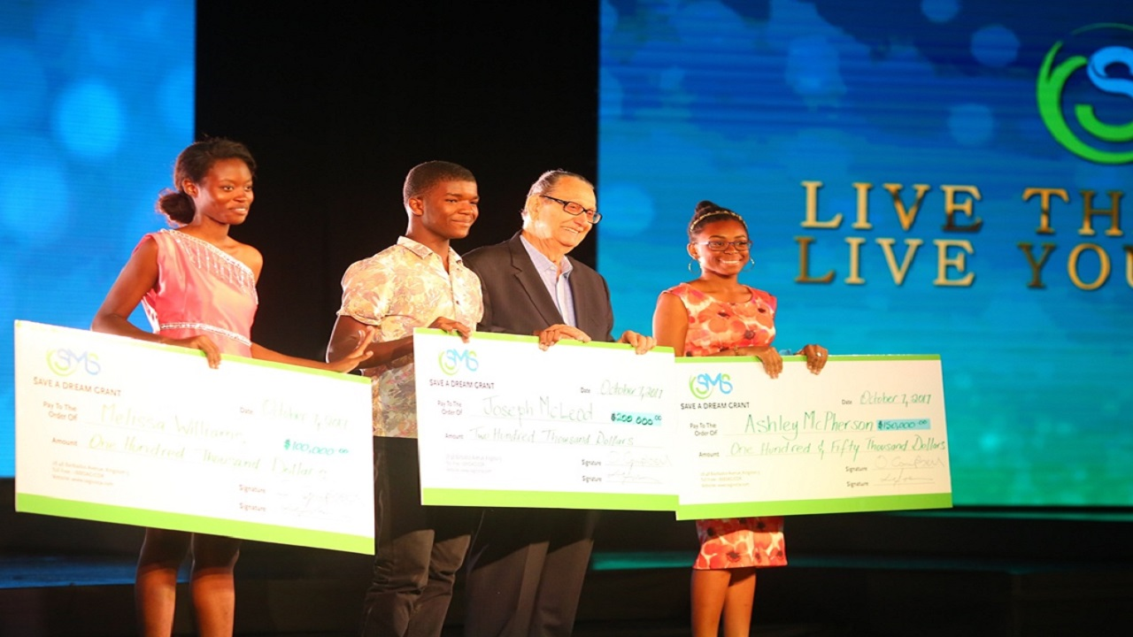 Sagicor Foundation Chairman R. Danny Williams (2nd right) shares in a photo-op with scholarship recipients Melissa Williams (left), Joseph McLeod (centre) and Ashley Morgan (right).