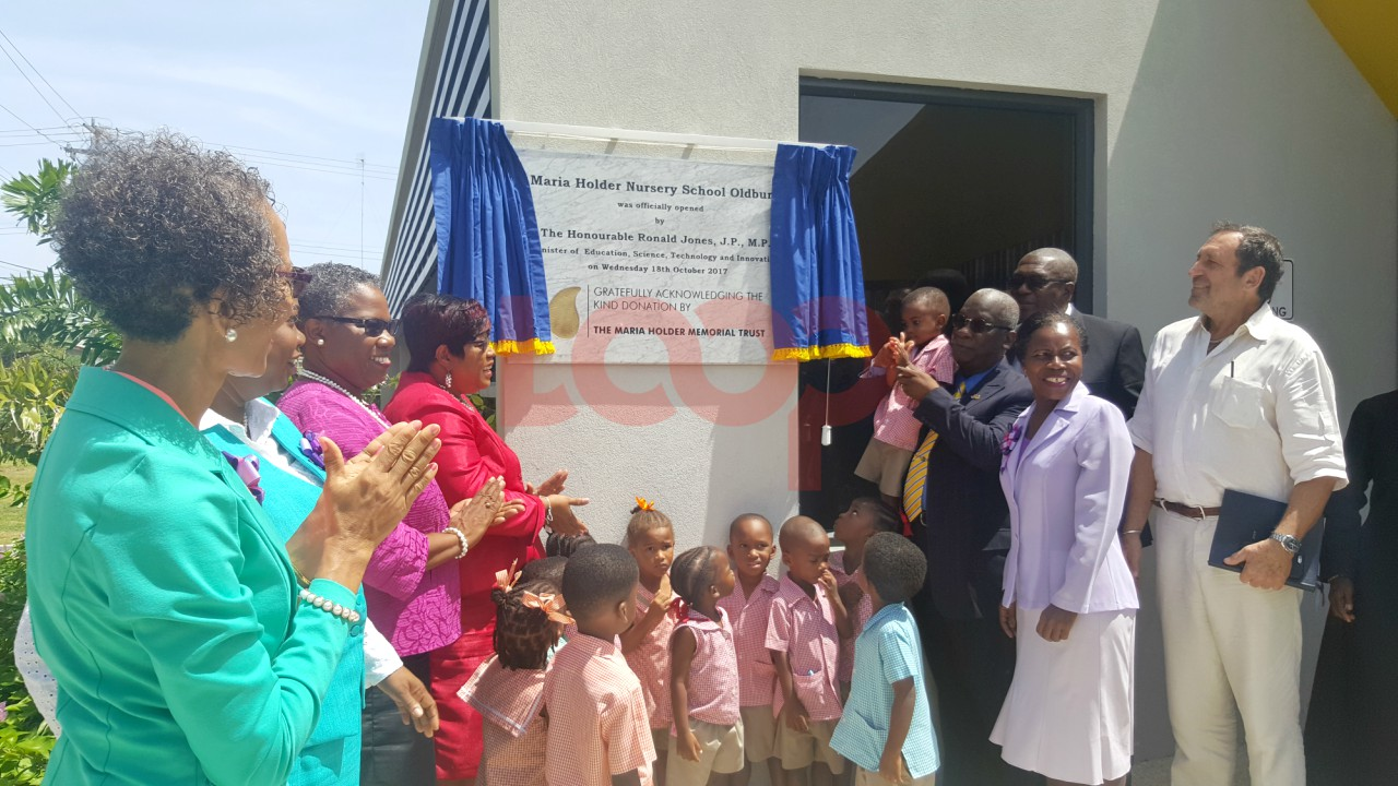 Minister of Education, Ronald Jones was ably assisted by one young student as he unveiled the official plaque at the Maria Holder Nursery School - Oldbury today.