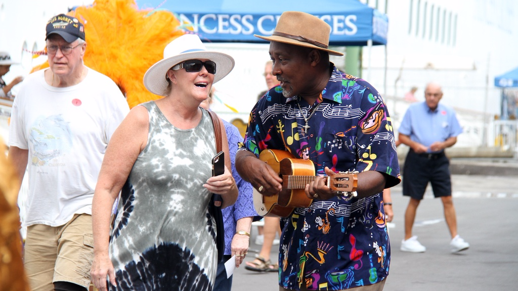 Calypsonian Black Sage serenades a tourist at the launch of the T&T Cruise Season