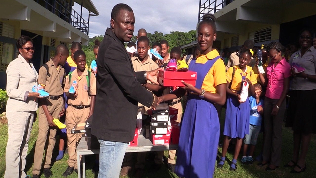 Founder and head of Trackalerts.com, Anthony Foster (left) presents a track and field spike to Ariel Robinson of Aberdeen High School on Friday. The presentation took place during devotion at the school. Robinson was one of two athletes, who represented the school at its first-ever Boys and Girls' Athletics Championships at the National Stadium in Kingston, earlier this year.