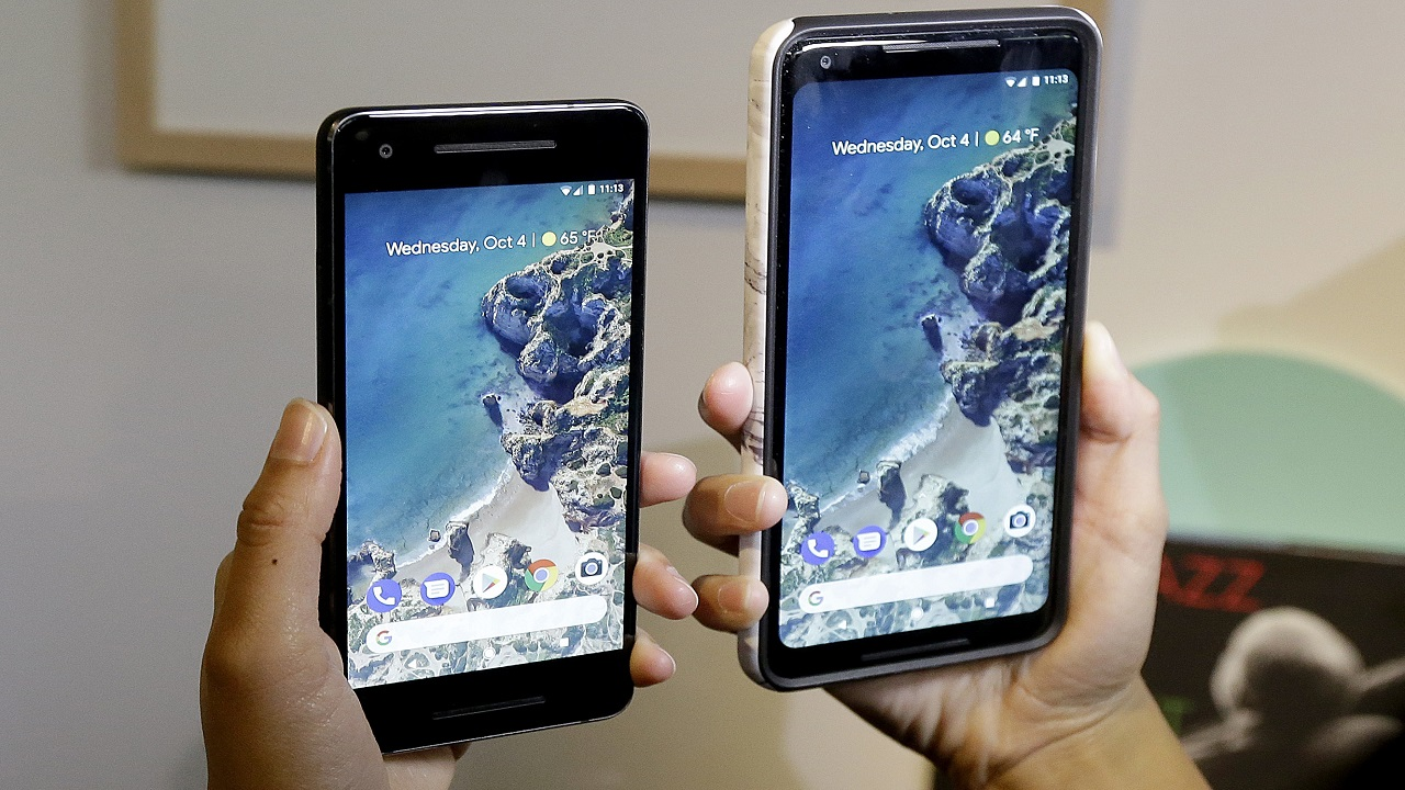 In this Wednesday, Oct. 4, 2017, file photo, a woman holds up the Google Pixel 2 phone, left, next to the Pixel 2 XL phone at a Google event at the SFJAZZ Center in San Francisco.