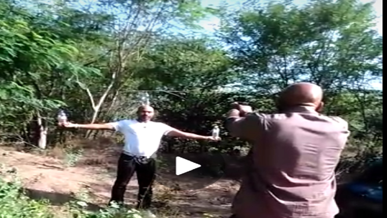 Screenshot of video showing politician Trevor Webb shooting at a bottle on a man's head.