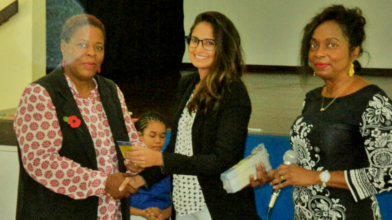 Caribbean Smilemakers Project Manager, Safiyya Kazi (centre), makes a donation to Principal of the St Gabriel's School, Angela Blackett. Looking on is Paula-Anne Moore, 2017 Fair Committee member.