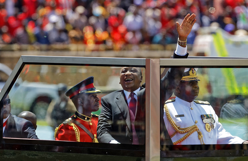 Kenyan President Uhuru Kenyatta waves from behind bulletproof glass as he arrives for his inauguration ceremony at Kasarani stadium in Nairobi, Kenya. (AP Photo/Ben Curtis)