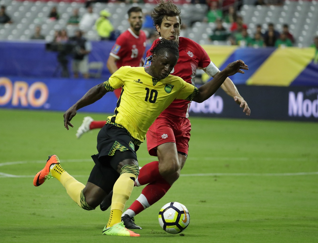 Jamaica's Darren Mattocks (10) dribbles past Canada's Dejan Jakovic during their CONCACAF Gold Cup quarterfinal match, Thursday, July 20, 2017, in Glendale, Ariz.