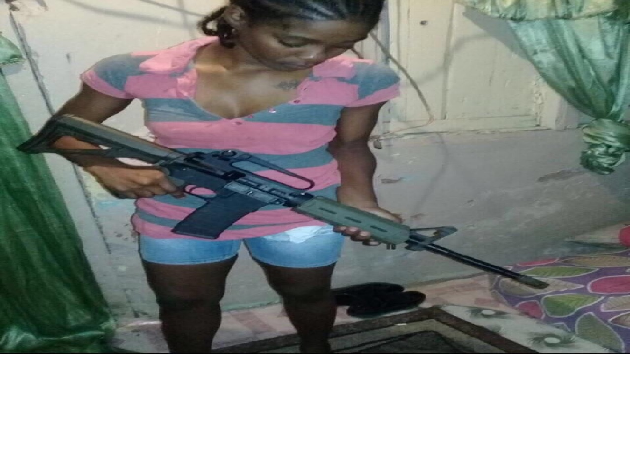 Photo showing the female posing with a high powered rifle
