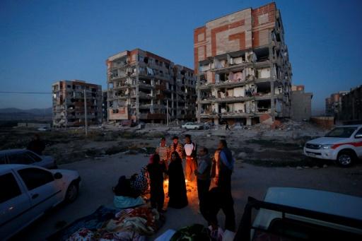 ISNA/AFP / POURIA PAKIZEH  Des Iraniens se réchauffent près d'un feu à Sar-e Pol-e Zahab le 13 novembre 2017 après un séisme qui a fait plus de 400 morts en Iran et en Irak.