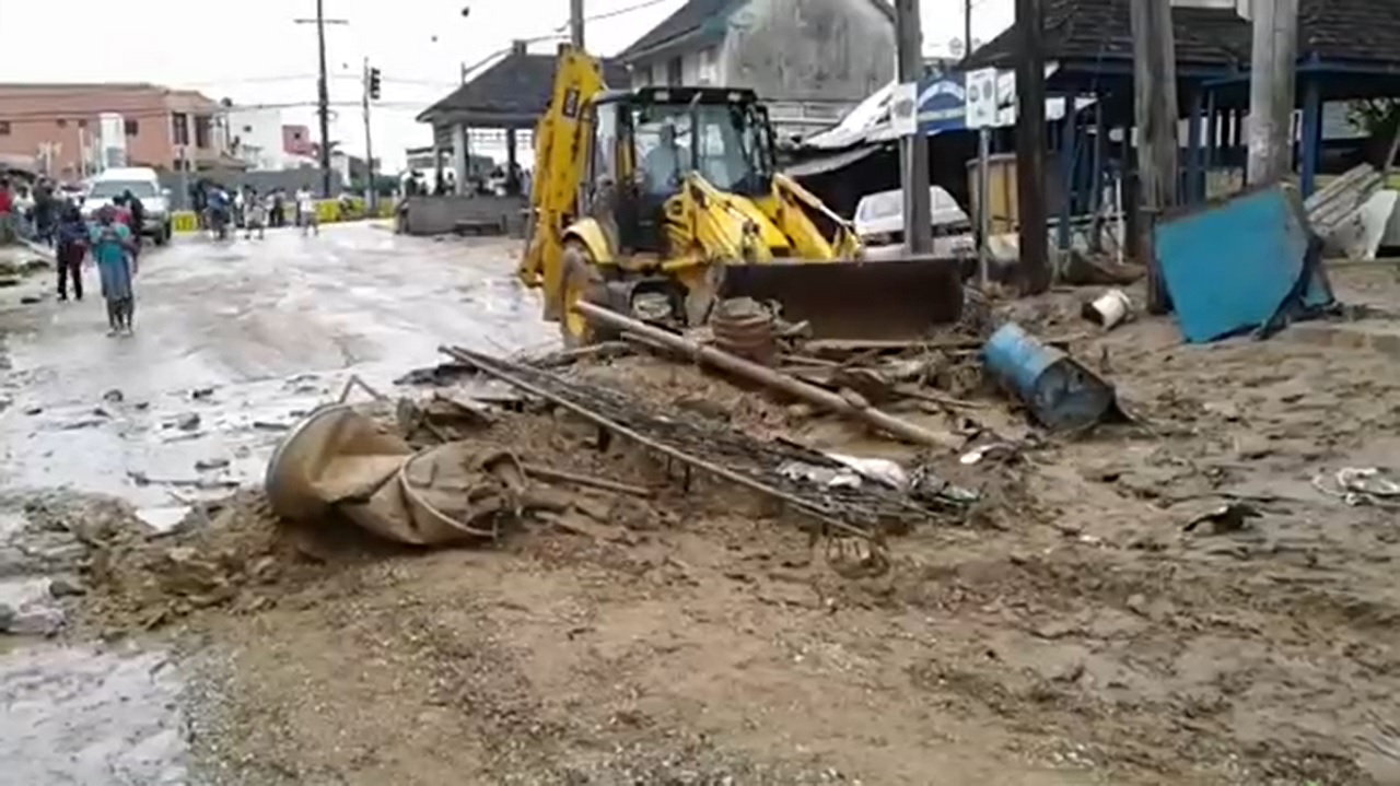 A tractor clears mud from a roadway in Montego Bay after flooding last week.