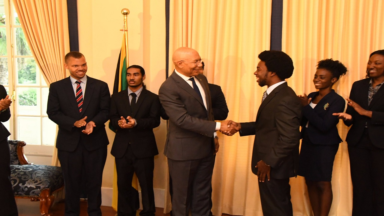 Jelani Munroe shakes hands with Governor General Sir Patrick Allen after being named Rhodes Scholar. (PHOTO: Kings House)