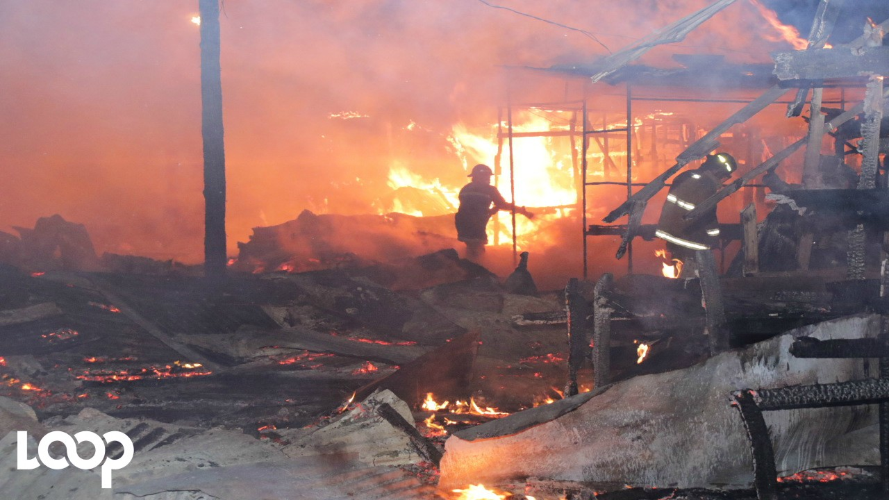 A firefighter bravely tackles the blaze at an informal market in downtown Kingston on Tuesday morning. (PHOTOS: Llewellyn Wynter)