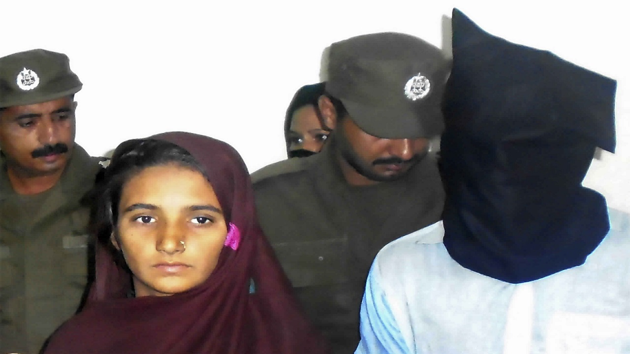 In this Monday, Oct. 30, 2017 photo, Aasia Bibi and her boyfriend, Shahid Lashari, are presented to journalists, at police station in Muzaffargarh in Pakistan. Pakistani police said Wednesday, Nov. 8, 2017, that they arrested a woman for allegedly plotting with Bibi, her newly married niece, to poison the 21-year-old woman's husband with tainted milk that would eventually kill him and 17 other relatives in a remote village.